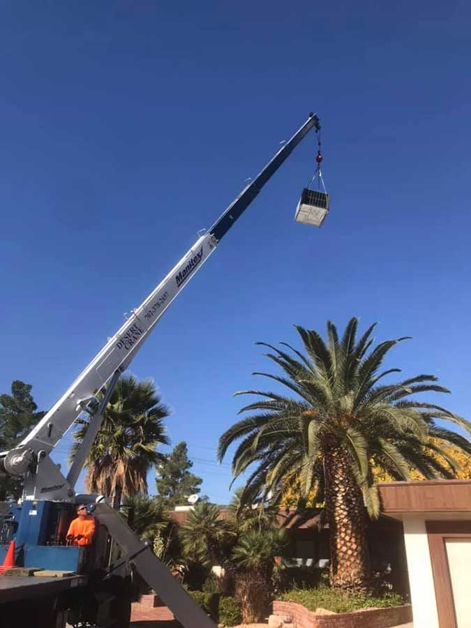 Crain lifting an air system above a home residence