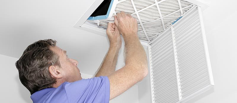 Man changing an air filter to improve the air quality